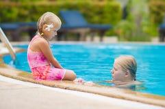 母亲和女儿有花的在耳朵后获得乐趣在水池边 免版税库存照片