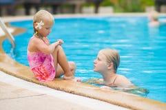 母亲和女儿有花的在耳朵后获得乐趣在水池边 图库摄影