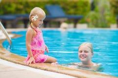 母亲和女儿有花的在耳朵后获得乐趣在水池边 库存图片