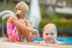 母亲和女儿有花的在耳朵后获得乐趣在水池边 免版税图库摄影