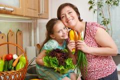 母亲和女儿有菜和新鲜水果的在厨房内部 父母和孩子 健康概念的食物 图库摄影