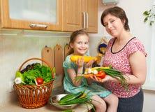 母亲和女儿有菜和新鲜水果篮子的在厨房内部 父母和孩子 健康概念的食物 库存图片