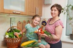 母亲和女儿有菜和新鲜水果篮子的在厨房内部 父母和孩子 健康概念的食物 库存照片