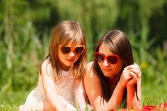 母亲和女儿有野餐在公园 免版税库存图片