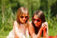 母亲和女儿有野餐在公园 库存照片