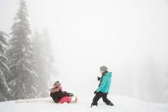 母亲和女儿有雪橇的 库存照片