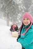 母亲和女儿有雪橇的 免版税图库摄影