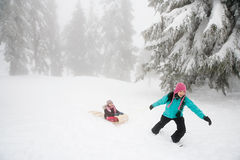 母亲和女儿有雪橇的 免版税库存图片