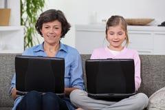 有计算机的母亲和女儿 库存图片