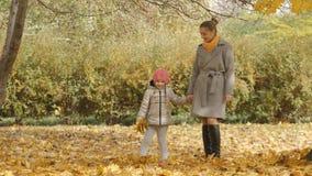母亲和女儿步行的在秋天停放 一起走以下落的秋天森林黄色离开 免版税图库摄影