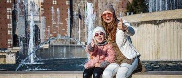 母亲和女儿游人在米兰,显示赞许的意大利 库存照片