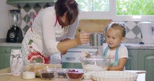 年轻母亲和女儿烘烤在厨房里 影视素材
