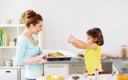 母亲和女儿烘烤松饼在家 免版税库存照片