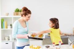 母亲和女儿烘烤松饼在家 库存图片