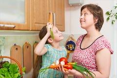 母亲和女儿烹调 菜和新鲜水果篮子在厨房内部 父母和孩子 健康概念的食物 库存图片