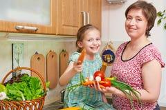 母亲和女儿烹调 菜和新鲜水果篮子在厨房内部 父母和孩子 健康概念的食物 免版税库存照片