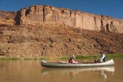 母亲和女儿独木舟的在沙漠河 库存照片