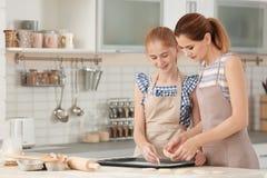母亲和女儿用曲奇饼面团在厨房里 库存图片