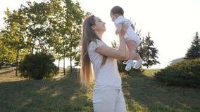 母亲和女儿的慢动作火光日落的 愉快的家庭的概念