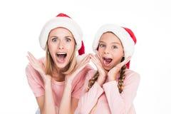 母亲和女儿看起来圣诞老人的帽子的激发, 免版税库存图片
