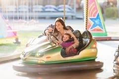 母亲和女儿碰撞用汽车的在游乐园 免版税库存图片