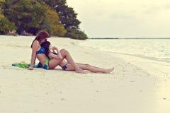 母亲和女儿神色向海洋 免版税库存图片