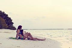母亲和女儿神色向海洋 免版税库存照片