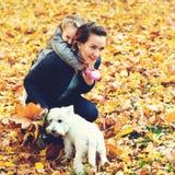 母亲和女儿秋天步行的与狗 获得愉快的爱恋的家庭乐趣 小白色一起享用狗和的家庭户外 免版税库存图片