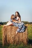 母亲和女儿秋天领域的与干草堆 免版税库存照片