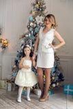 母亲和女儿站立在圣诞树的三年 图库摄影