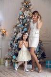 母亲和女儿站立在圣诞树的三年 库存照片