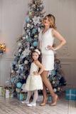 母亲和女儿站立在圣诞树的三年 免版税库存图片