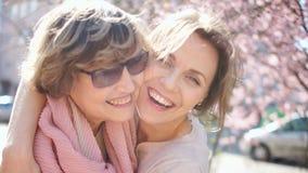 母亲和女儿美丽的晴朗的春天画象  拥抱和笑反对太阳强光背景的两名妇女  股票视频