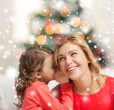 母亲和女儿耳语的闲话 免版税库存图片