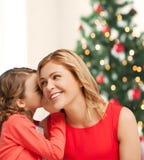母亲和女儿耳语的闲话 免版税库存照片