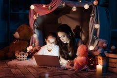 母亲和女儿膝上型计算机的在枕头在晚上在家后安置 库存图片