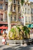 母亲和女儿获得乐趣在喷泉石头在中心o 免版税图库摄影