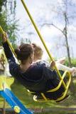 母亲和女儿获得乐趣在摇摆的儿童公园 图库摄影