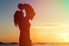 母亲和女儿获得乐趣在日落海滩 免版税库存照片