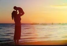 母亲和女儿获得乐趣在日落海滩 图库摄影