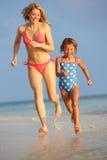 母亲和女儿获得乐趣在海滩假日的海 库存照片