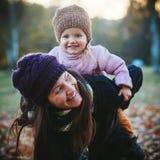 母亲和女儿获得乐趣在秋天公园 库存照片