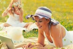 母亲和女儿获得在草甸的乐趣在春天 库存照片