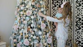 母亲和女儿装饰并且敬佩一棵圣诞树 股票视频
