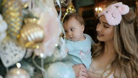 母亲和女儿装饰并且敬佩一棵圣诞树 影视素材