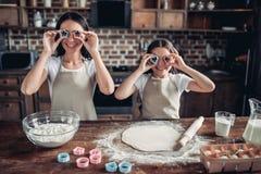 母亲和女儿覆盖物注视与曲奇饼切削刀 免版税库存图片