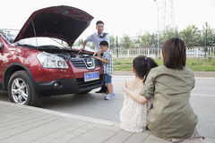 母亲和女儿观看当父亲和儿子尝试修理汽车 库存图片