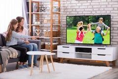 母亲和女儿观看的电视在客厅 库存照片