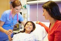 母亲和女儿谈话与女性护士在医房 免版税库存图片