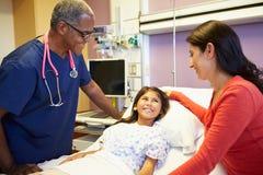 母亲和女儿谈话与男性护士在医房 免版税图库摄影